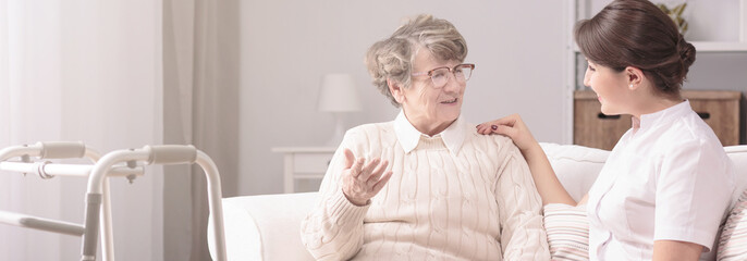 Panorama of a senior woman talking to a young, female caregiver in a private rehabilitation center
