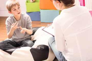 Little boy with learning difficulties talking to a child psychologist