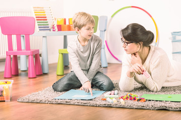 Private tutor and a small boy learning and playing at home. Fun teaching concept