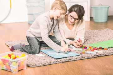 Single mother spending time with her son by drawing together on a fluffy carpet