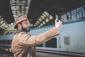 Handsome businessman making selfie on a mobile phone.Casual professional entrepreneur using smartphone outside while waiting train on railway station