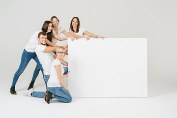 Group of friendly people posing with a blank sign