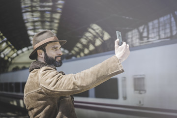 Attractive adult businessman making selfie on a mobile phone.Casual professional entrepreneur using smartphone outside while waiting train on railway station