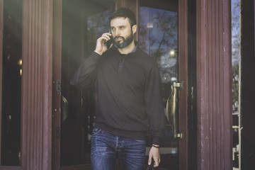 Casual professional entrepreneur using smartphone outside.Bearded Man in talking on a mobile phone.Sunlights effects