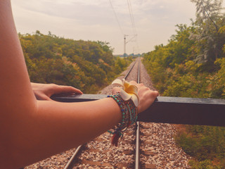 Female tourist looking at the railway track from the train.