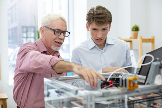 Sharing knowledge. Experienced senior engineer instructing his young intern about 3D printers while pointing at the important parts of mechanism