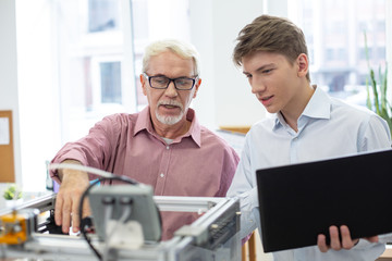 Nice teacher. White-haired senior engineer teaching his young student about 3D printers and telling him about the work algorithm
