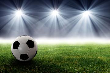 Fußball liegt auf dem Rasen vor Flutlicht Strahlern