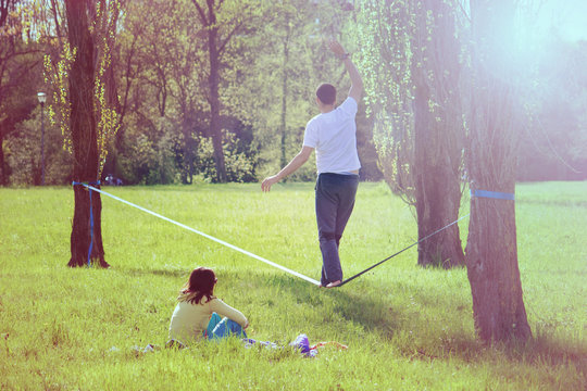 balancing exercise with tightrope, young man having fun in a park walking on a wire (a girl sitting on the grass looking the action)