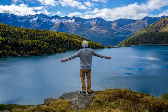 guy standing on a cliff with beautiful mountain lake view