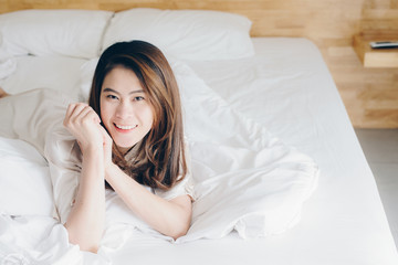 Portrait of asian woman lying on bed.