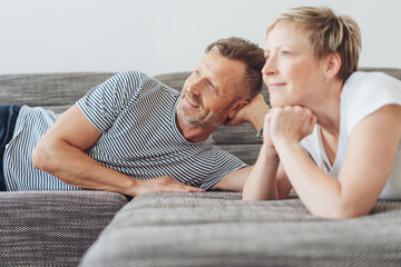 Couple relaxing at home on a sofa watching TV