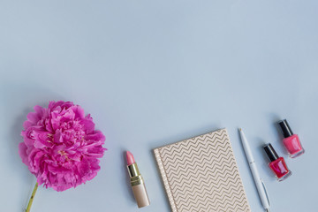 Flat lay desk with pink peony, cosmetics and accessories