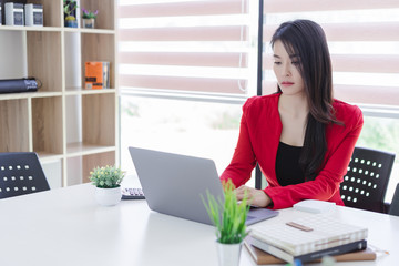 Beautiful attractive young asian business woman working with laptop at meeting or negotiation in the office.