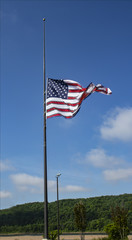 Large American Flag flown a half staff as a symbol for as a symbol of respect or mourning making room for invisible flag a death above