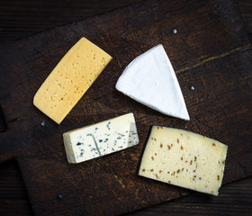 pieces of different cheeses on a brown wooden board: