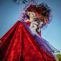 Fairy tale woman on stilts in bright fantasy stylization. Fine art outdoor photo.