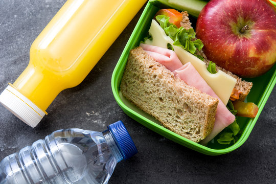 Healthy school lunch box: Sandwich, vegetables ,fruit and juice on black stone. Top view