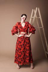 Красивая девушка с темными волосами в красном платье стоит на бежевом фоне