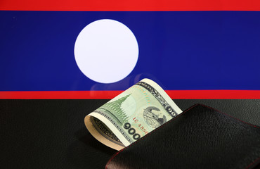 Poster Chicken One thousand of banknote currency Lao Kip with black wallet on the black floor with Laos nation flag background. It is the money of Laos in 1999, and the concept of finance.