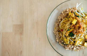 Top view of fried Pad Thai noodles with tofu traditional Asian food on wooden table background