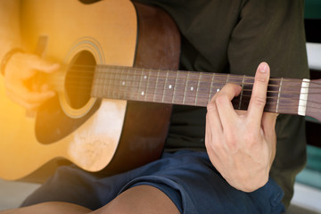 Close up soft focus and blur guitarist's hand is holding the chord B on acoustic guitar fretboard in time to relax