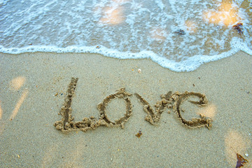 Write the word love on the beach. Soft focus wave.