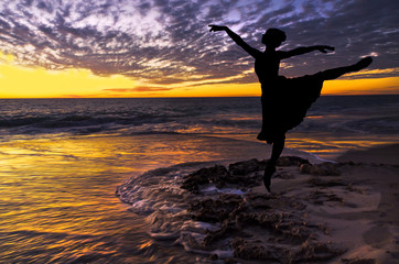 Silhouette of a ballet dancer at the beach at sunset