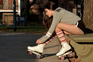 Side view of a young woman getting ready for skating outdoors