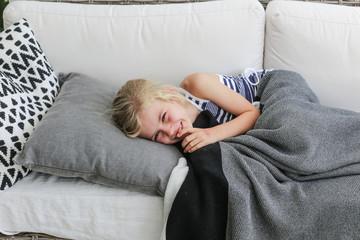 Girl lying on a sofa laughing,