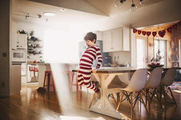 Boy jumping off a dining room table