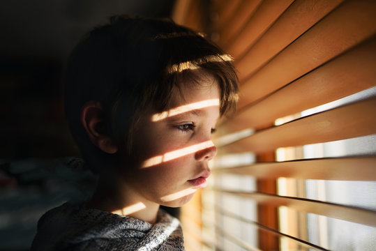 Boy standing by a window looking through blinds