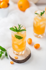 Fresh summer cocktail with orange juice and ice cubes. Glass of orange soda drink on white background