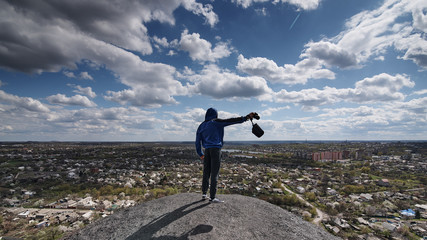 A photographer with a camera stands on a hill and looks at the city below.