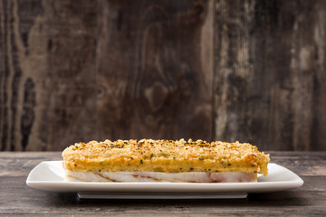 White fish casserole with cheese on wooden background.