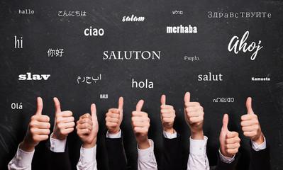 """viele Daumen Hoch und """"Hallo"""" in vielen Sprachen auf Kreidetafel"""