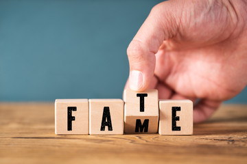 "Hand flips a cube with letters and turns the word ""FATE"" into ""FAME"""