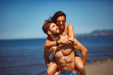 Young happy couple in a embrace on the beach