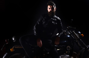 Macho, brutal biker in leather jacket stand near motorcycle at night time, copy space. Biker culture concept. Man with beard, biker in leather jacket lean on motor bike in darkness, black background.