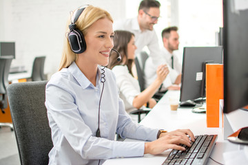 Smiling woman customer support operator using computer in office