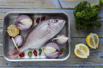 Overhead view of fish, vegetable, and spices in tray