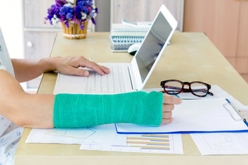 working woman with green cast on arm working on laptop in office, focus on broken hand