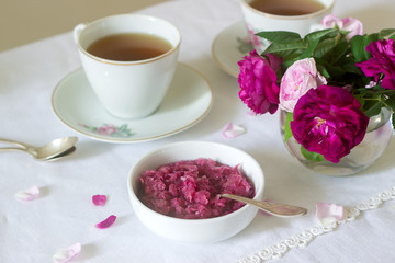 Jam from the petals of the Damascus rose, a cup of green tea and a vase of roses on a light table. Rustic style.