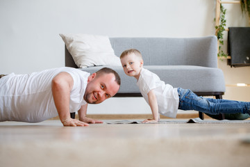 Photo of happy dad and son pushing on floor
