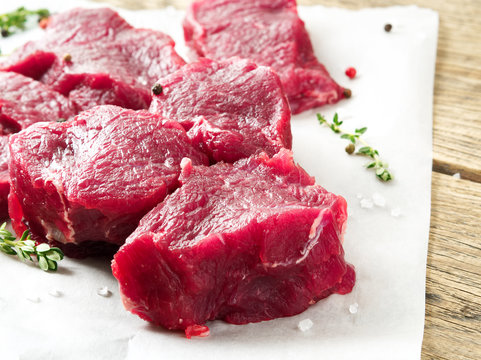 Pieces of raw meat. Raw beef with spices and thyme on wooden rough rustic background, side view, close-up.