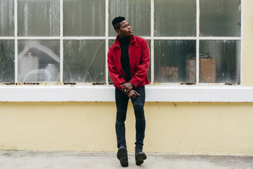 Stylish young black man in red jacket in a glasses wall
