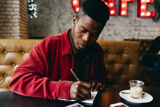 Black man sitting in cafe and writing