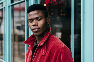 Young black man in red jacket standing by cafe