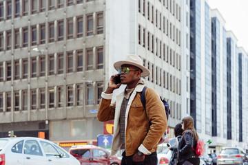 Black man in glasses using his smartphone
