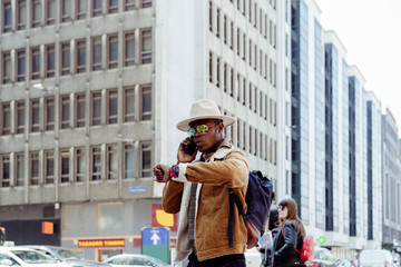 Black man in glasses using his smartphone